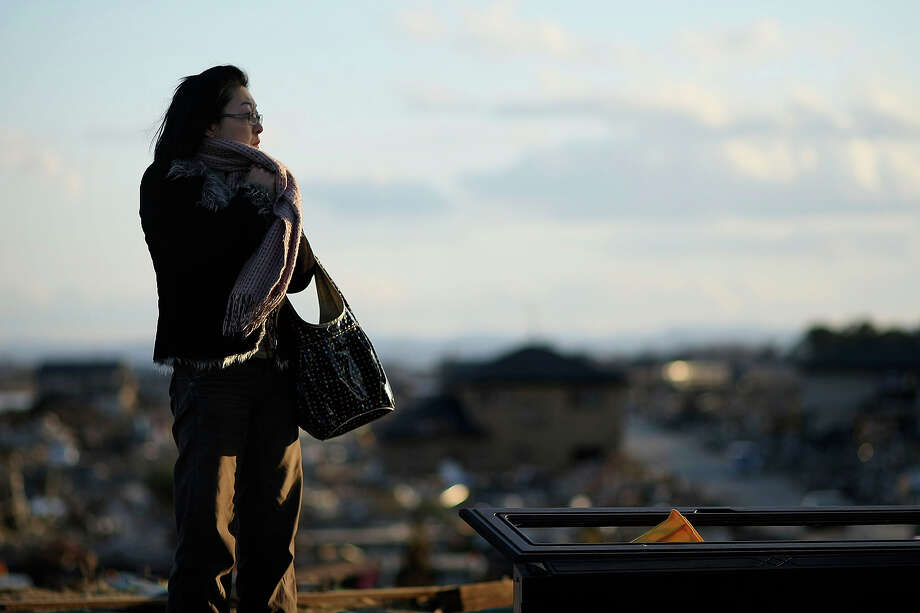 "In this photo taken Sunday, March 27, 2011, a woman looks out to the destroyed neighborhoods from atop Weather Hill in Natori, Miyagi Prefecture, northeastern Japan. The hill was originally built to give fishermen a view of sea conditions but now offers an unforgettable look out over the vastness of the mass destruction left from tsunami caused by the March 11 earthquake. More than two weeks after the tsunami devastated communities along Japan's coast, the neighborhood around ""Hiyori Yama"" - Weather Hill - is beginning to show signs of life. (AP Photo/Wally Santana) Photo: Wally Santana, ASSOCIATED PRESS / AP2011"