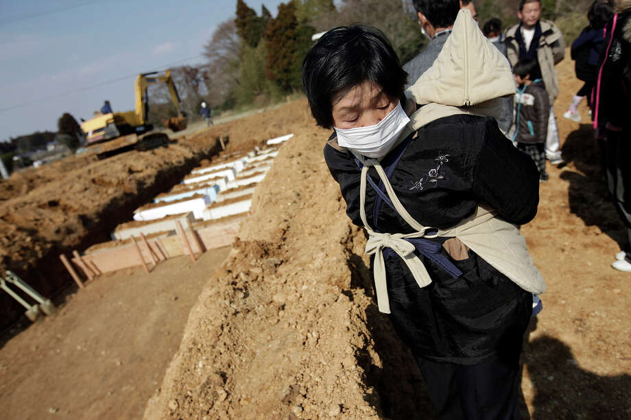 A woman with a baby on her back stands near coffins of  victims of the March 11 earthquake and tsunami at a mass grave site in Yamamoto, Miyagi Prefecture, northeastern Japan, Tuesday, March 29, 2011. Photo: Eugene Hoshiko, AP / AP