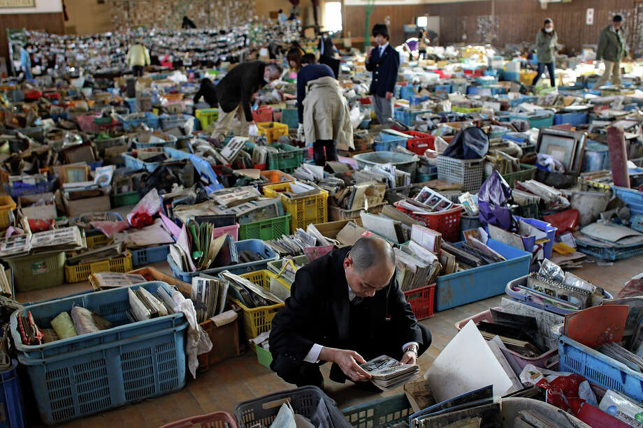 Japanese search for family albums and belongings among a pile of items recovered from the area devastated by the March 11 earthquake and tsunami and displayed at a school gymnasium in Natori, Miyagi Prefecture, Japan, Wednesday, April 13, 2011. Volunteers have been cleaning photos and personal possessions retrieved from damaged homes in the hope that they can be returned to survivors of the tsunami. (AP Photo/Sergey Ponomarev) Photo: Sergey Ponomarev, ASSOCIATED PRESS / AP2011