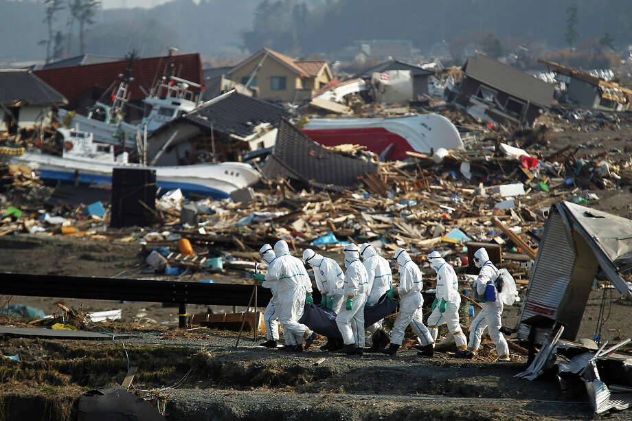 FILE - In this April 15, 2011 file photo, Japanese police officers carry a body during a search and recovery operation for missing victims in the area devastated by the March 11 earthquake and tsunami in Namie near the tsunami-crippled Fukushima Dai-ichi nuclear power plant in Fukushima Prefecture, northeastern Japan. Japanese nuclear regulators trusted that the reactors at Fukushima Dai-ichi were safe from the worst waves an earthquake could muster based on a single-page memo from the plant operator nearly a decade ago. The towering waves unleashed by the magnitude-9.0 earthquake on March 11 destroyed backup generators for several reactors' cooling systems, and the nuclear cores in three reactors melted, sparking the worst atomic crisis the world since Chernobyl. Workers have yet to bring the plant under control more than two months later. (AP Photo/Hiro Komae, File) Photo: Hiro Komae, ASSOCIATED PRESS / AP2011