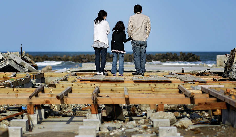 Tsutomu Murai, 31, right, with his wife Makiko, 28, and daughter Haruna, 8, watch the Pacific Ocean as they stand on the basement of their house washed out by tsunami wave in the area devastated by the March 11 tsunami and earthquake in the town of Soma, Fukushima Prefecture, Japan, Sunday, April 24, 2011. (AP Photo/Sergey Ponomarev) Photo: Sergey Ponomarev, ASSOCIATED PRESS / AP2011