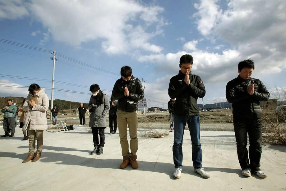 People observe a moment of silence in front of what is left of a disaster control center in an area devastated by the March 11, 2011 earthquake and tsunami, in Minamisanriku, Miyagi prefecture, in Japan, Monday, March 11, 2013. Japan marked the second anniversary on Monday of the devastating earthquake and tsunami that left nearly 19,000 people dead or missing.(AP Photo/Shizuo Kambayashi) Photo: Shizuo Kambayashi, ASSOCIATED PRESS / AP2013