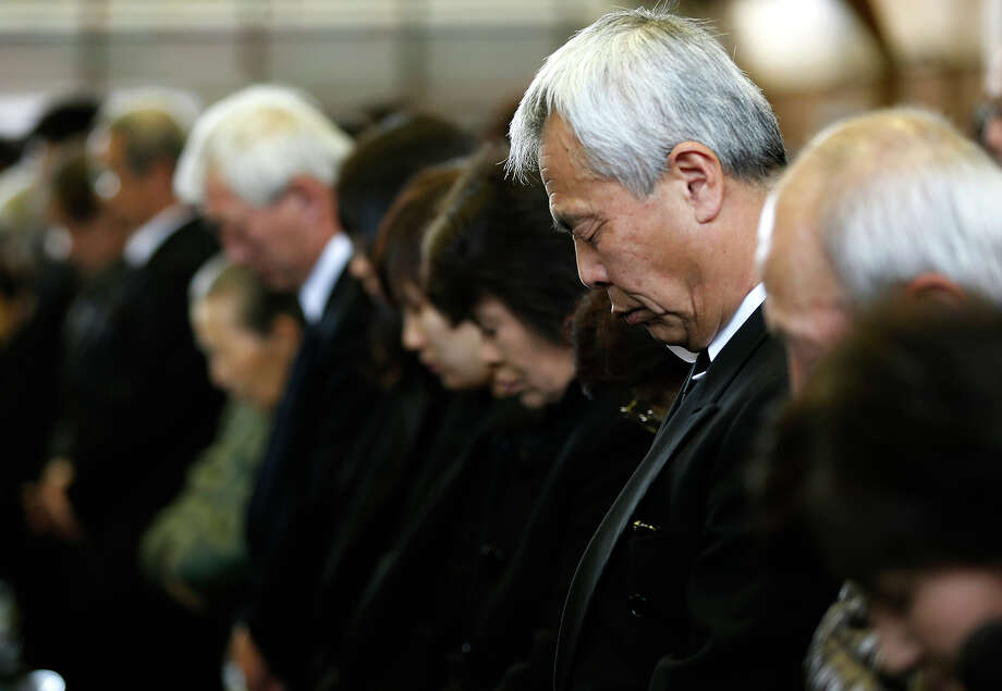 People pray in silence at a memorial service honoring victims of the March 11, 2011 earthquake and tsunami, a day before the second anniversary of the disaster, in Rikuzentakata, Iwate Prefecture, northern Japan, Sunday, March 10, 2013. (AP Photo/Shizuo Kambayashi) Photo: Shizuo Kambayashi, ASSOCIATED PRESS / AP2013