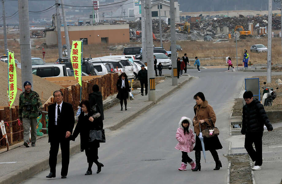 People make their way to a memorial service in remembrance of victims of the March 11, 2011 earthquake and tsunami, a day before the second anniversary of the disaster, in Rikuzentakata, Iwate Prefecture, northern Japan, Sunday, March 10, 2013. (AP Photo/Shizuo Kambayashi) Photo: Shizuo Kambayashi, ASSOCIATED PRESS / AP2013
