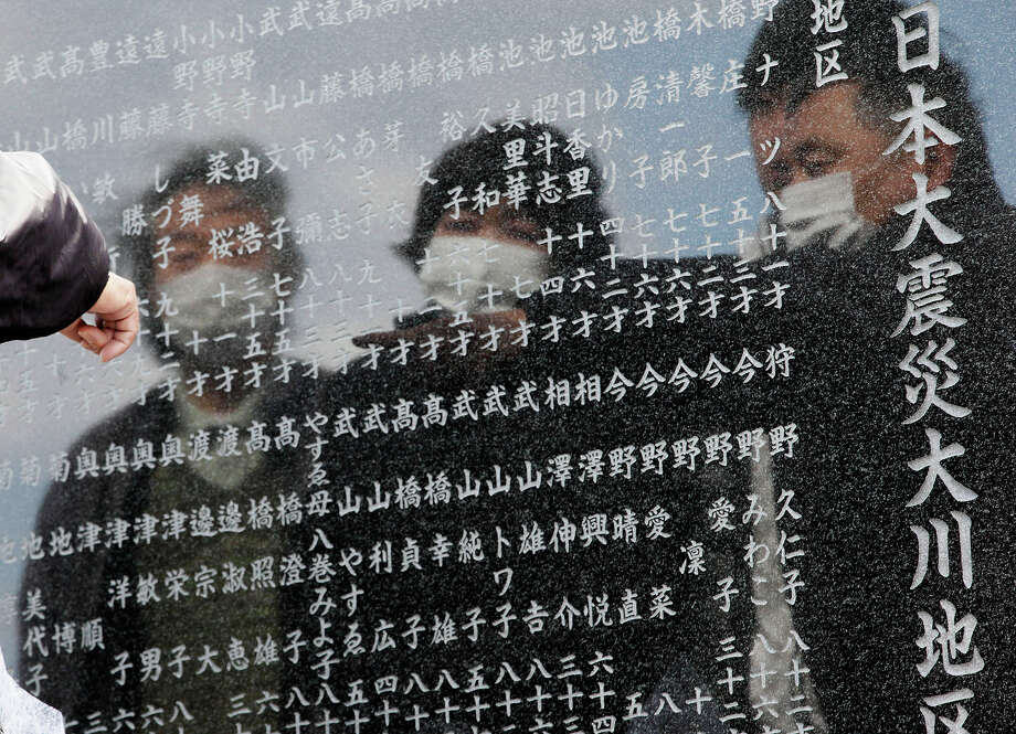 A man points to the name of one of the victims of the earthquake and tsunami inscribed in a cenotaph in Okawa district in Ishinomaki, Miyagi Prefecture, northern Japan, Monday, March 11, 2013. Japan marked the second anniversary on Monday of a devastating earthquake and tsunami that left nearly 19,000 people dead or missing. (AP Photo/Shizuo Kambayashi) Photo: Shizuo Kambayashi, ASSOCIATED PRESS / AP2013
