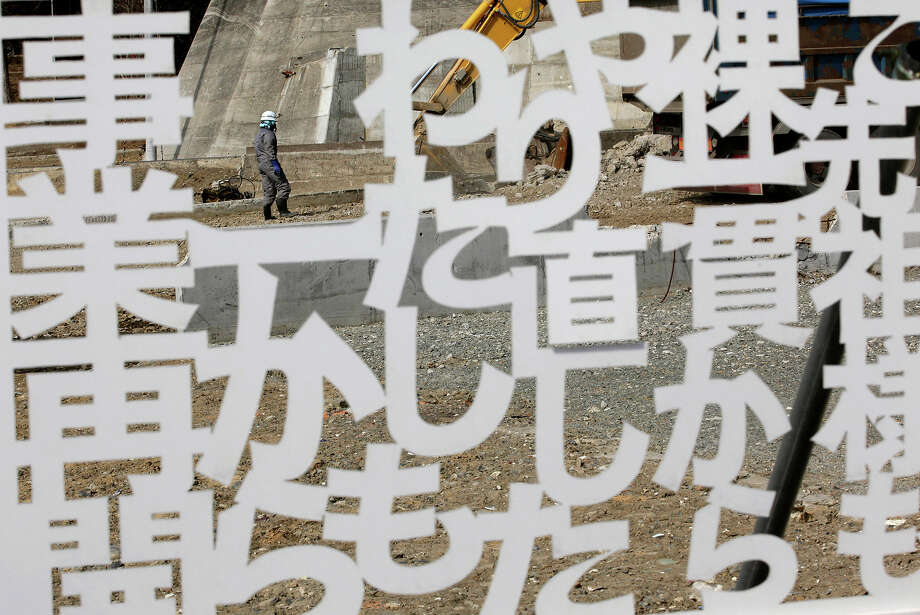 A worker walks behind a white plastic plate cutout of the words of a local businessperson, declaring determination to reopen the business, in a tsunami-stricken area in Minamisanriku, Miyagi prefecture, northern Japan, Monday, March 11, 2013. Japan marked the second anniversary on Monday of a devastating earthquake and tsunami that left nearly 19,000 people dead or missing. The words mean; I will restart my business from zero like my ancestor. (AP Photo/Shizuo Kambayashi) Photo: Shizuo Kambayashi, ASSOCIATED PRESS / AP2013
