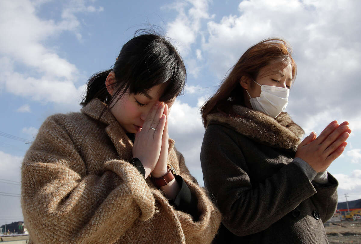 People offer prayer in a moment of silence in front of what is left of a disaster control center in an area devastated by the March 11, 2011 earthquake and tsunami in Minamisanriku, Miyagi Prefecture, Monday, March 11, 2013. Japan marked the second anniversary on Monday of the devastating disasters that left nearly 19,000 people dead or missing. (AP Photo/Shizuo Kambayashi)