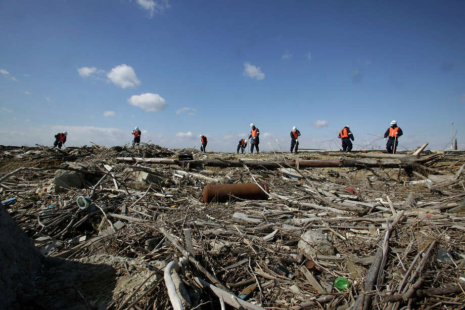 Police officers search for the remains of those who went missing in the March 11, 2011 tsunami on the coastline in Ishinomaki, Miyagi Prefecture, northern Japan, Monday, March 11, 2013. The two-year anniversary Monday of Japan's devastating earthquake, tsunami and nuclear catastrophe is serving to spotlight the stakes of the country's struggles to clean up radiation, rebuild lost communities and determine new energy and economic strategies.(AP Photo/Shizuo Kambayashi) Photo: Shizuo Kambayashi, ASSOCIATED PRESS / AP2013