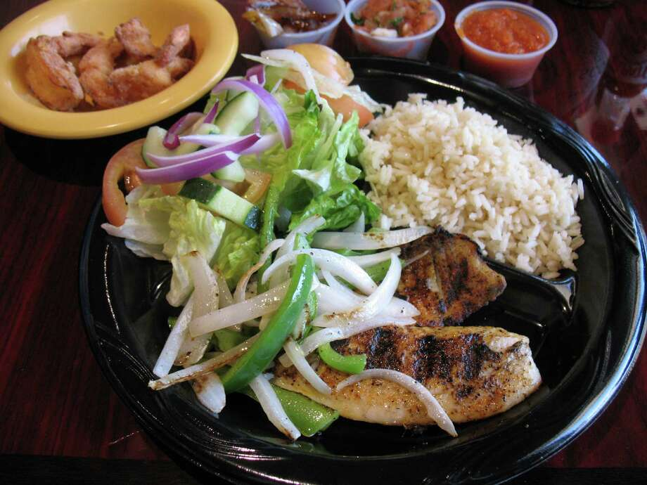 A daily special of tilapia and fried shrimp is served with a salad, rice and a drink at Fish & Grill Seafood House.