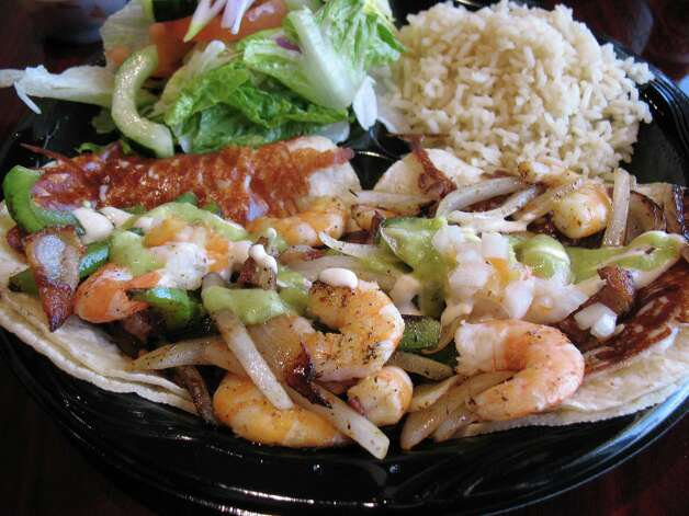 A daily special of tilapia and fried shrimp is served with a salad and rice at Fish & Grill Seafood House.