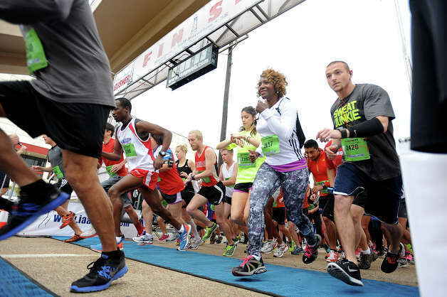 Runners take off from the start of the 5K race in front of the Montagne Center on Saturday.  2013 Gusher Marathon and 5K Photo taken March, 09, 2013 Guiseppe Barranco/The Enterprise Photo: Guiseppe Barranco, STAFF PHOTOGRAPHER / The Beaumont Enterprise