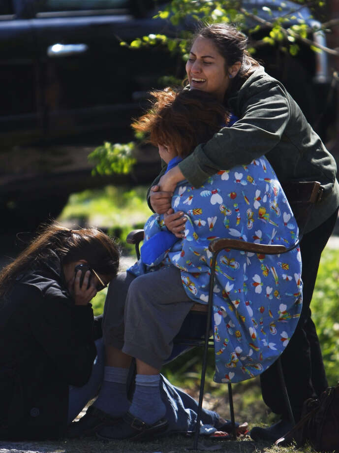 Friends and family members gather outside a home after a homicide took place in the 3700 block of Sparks Street. Photo: .
