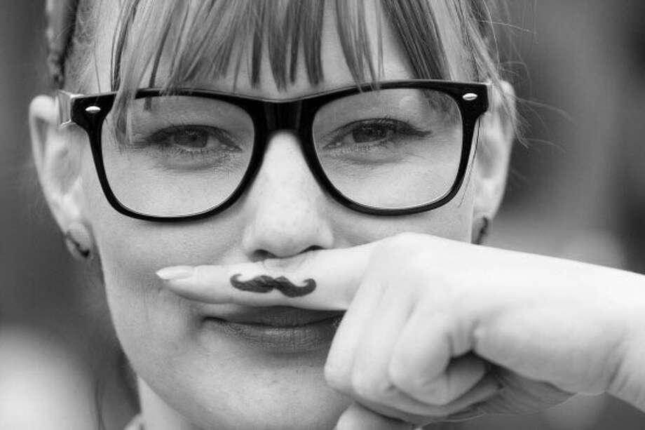 Hipster with beatnik glasses and an ironic mustache. Photo: Adam Berry, Getty / 2012 Getty Images
