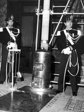 1939: Two papal guards are watching over the Vatican stove.  The role of the stove is essential in every election: in case of a non-unanimous vote, the ballots are burned in this stove with dampened straw which produces black smoke. This informs the people of Rome that the pope has not yet been elected. In case of a unanimous vote, the ballots are burned without the straw and the people see white smoke coming from the Vatican and so learn that the new pope has been elected unanimously. Photo: Keystone-France, Gamma-Keystone Via Getty Images / KEYSTONE-FRANCE