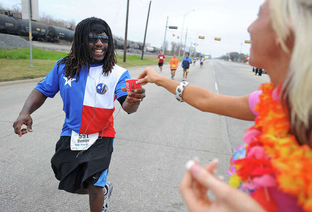 Kelsey Perritt hands out water to runners on Martin Luther King Parkway during the Gusher Marathon. 2013 Gusher Marathon and 5K Photo taken March, 09, 2013 Guiseppe Barranco/The Enterprise Photo: Guiseppe Barranco, STAFF PHOTOGRAPHER / The Beaumont Enterprise