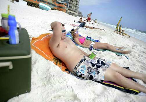 Hunter Mason, left, and Olivia Murat, on spring break from the University of Indianapolis, relax on the beach Tuesday March 5, 2013 in Destin, Fla. Photo: Nick Tomecek, Associated Press / Northwest Florida Daily News