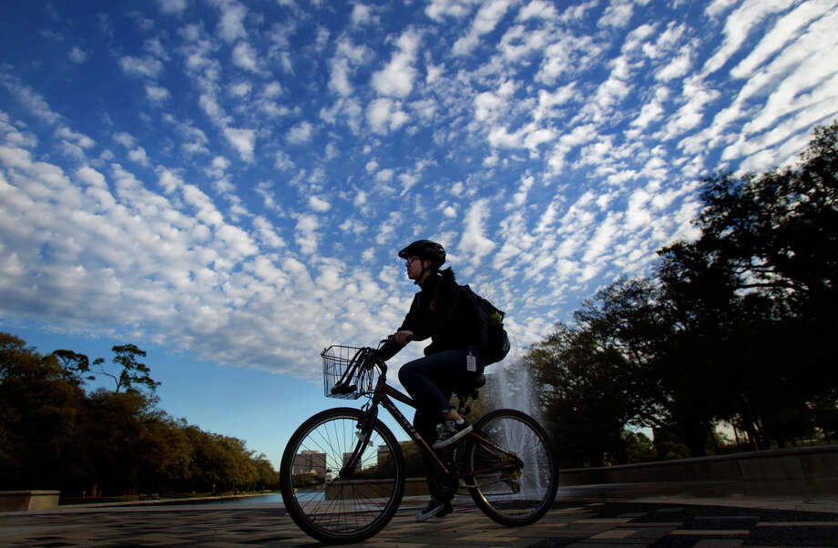 A woman rides a bike through Hermann Park as the sun rises, Monday, March 11, 2013, in Houston. The forecast calls for sunny skies with with temperatures reaching into the low to middle 60s. Photo: Cody Duty, Houston Chronicle / © 2013 Houston Chronicle