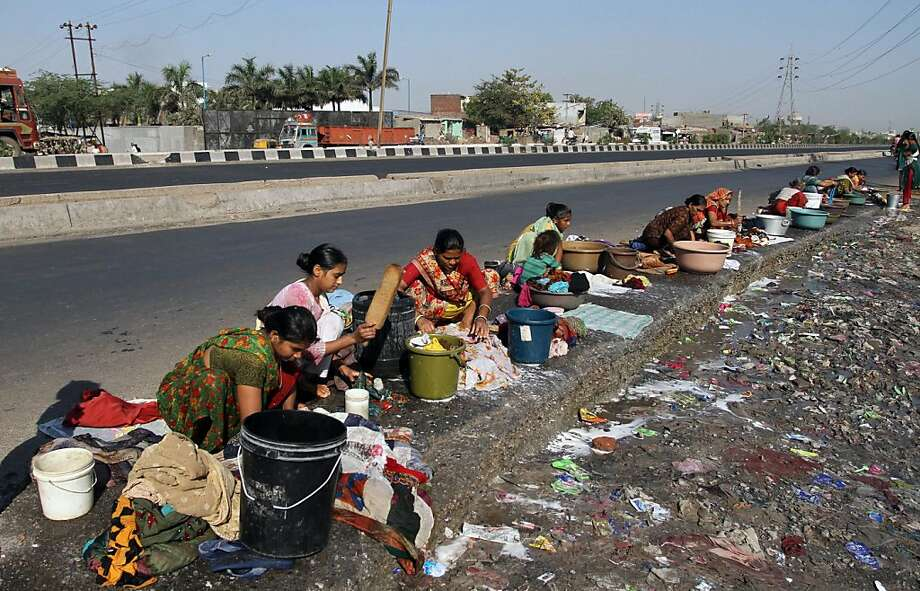 Laundry day: Indian women scrub clothes on the asphalt of a highway outside Rajkot, Gujarat state. Photo: Ajit Solanki, Associated Press