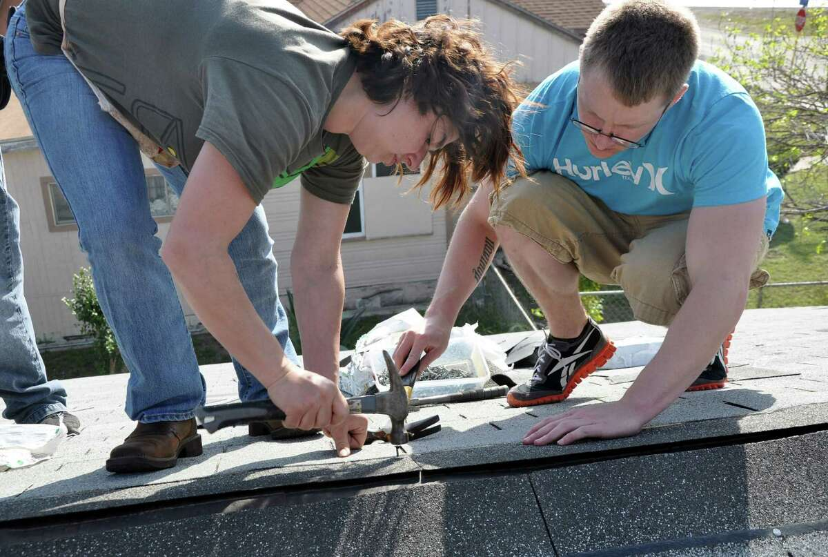 Sgt. Courtney Jennings and Sgt. Tyler Burke collaborate on a section of roof on a Habitat for Humanity house Feb. 21.