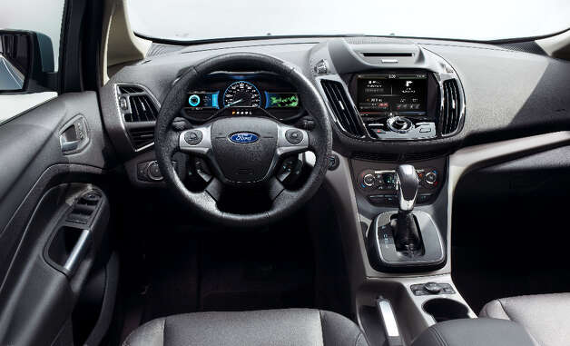 2013 Ford C-MAX Hybrid dash layout has a small window, to the right of the speedometer, displaying green Efficiency Leaves, to let you know you're driving a hybrid / © 2012 Ford Motor Company