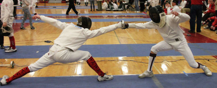 Fairfield fencer George Whiteside, left, scores a point against a Hopkins School fencer during epee competition Saturday in North Haven. Photo: Contributed Photo / Fairfield Citizen