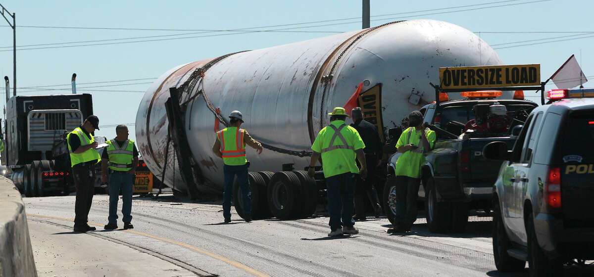 Police and other workers tend to the scene of a large tanker accident that took place Monday March 11, 2013 before 1:00 p.m. on southbound Loop 410 near Binz-Engleman Road. Police at the scene said the empty tank weighs 117,000 pounds and became detatched from its trailer after hitting a concrete barrier. There were no injuries during the incident.