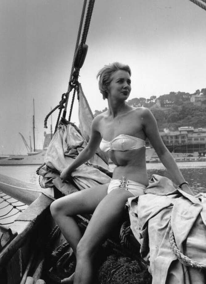 1955:  A model wearing a swimsuit sits at the prow of a yacht touring the French Riviera.  Photo: Bert Hardy, Getty / Picture Post