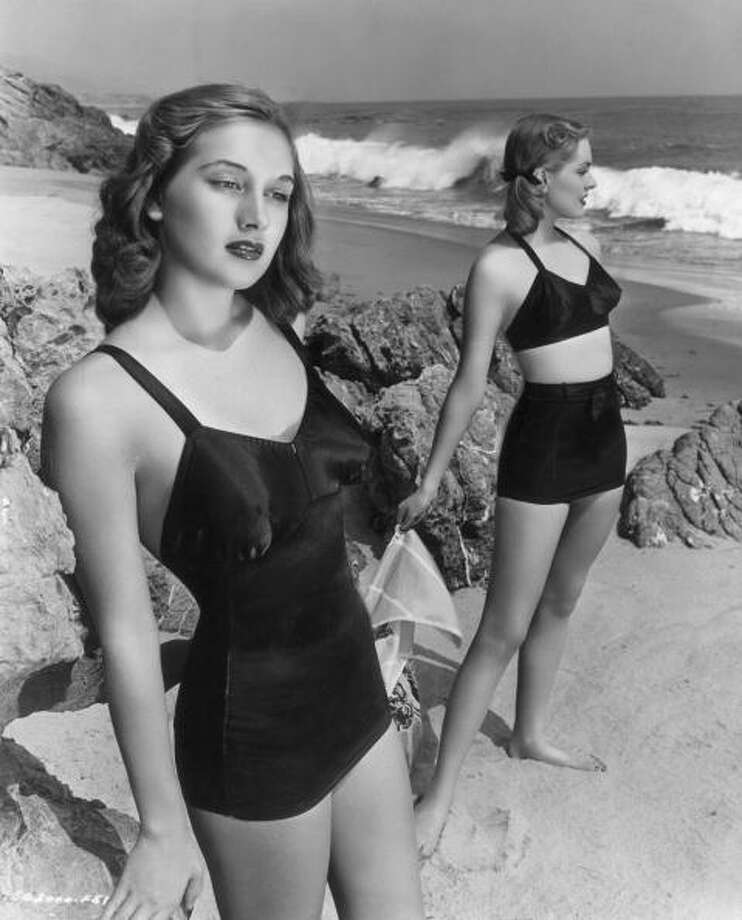 1947:  Model and actor Georgia Lange (left), one of the 'Goldwyn Girls,' wears a one-piece black satin latex bathing suit on a beach, as another woman in a two-piece suit poses behind her. Photo: Hulton Archive, Getty / Archive Photos