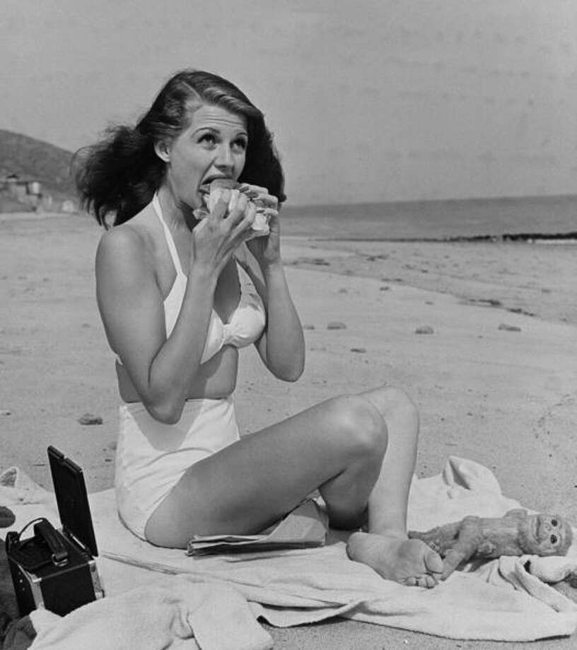1941: Actress Rita Hayworth taking a bite out of a hamburger as she sunbathes in a white two-piece bathing suit. Photo: Bob Landry, Getty / Bob Landry