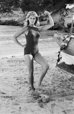 1968: Actress Candice Bergen strikes a pose on a beach. She is resting one foot on a dog in the sand. Photo: Terry O'Neill, Getty / 2005 Getty Images
