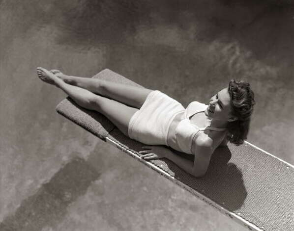 1940s: A woman lying on a diving board over a pool  Photo: H. Armstrong Roberts, Getty / Retrofile