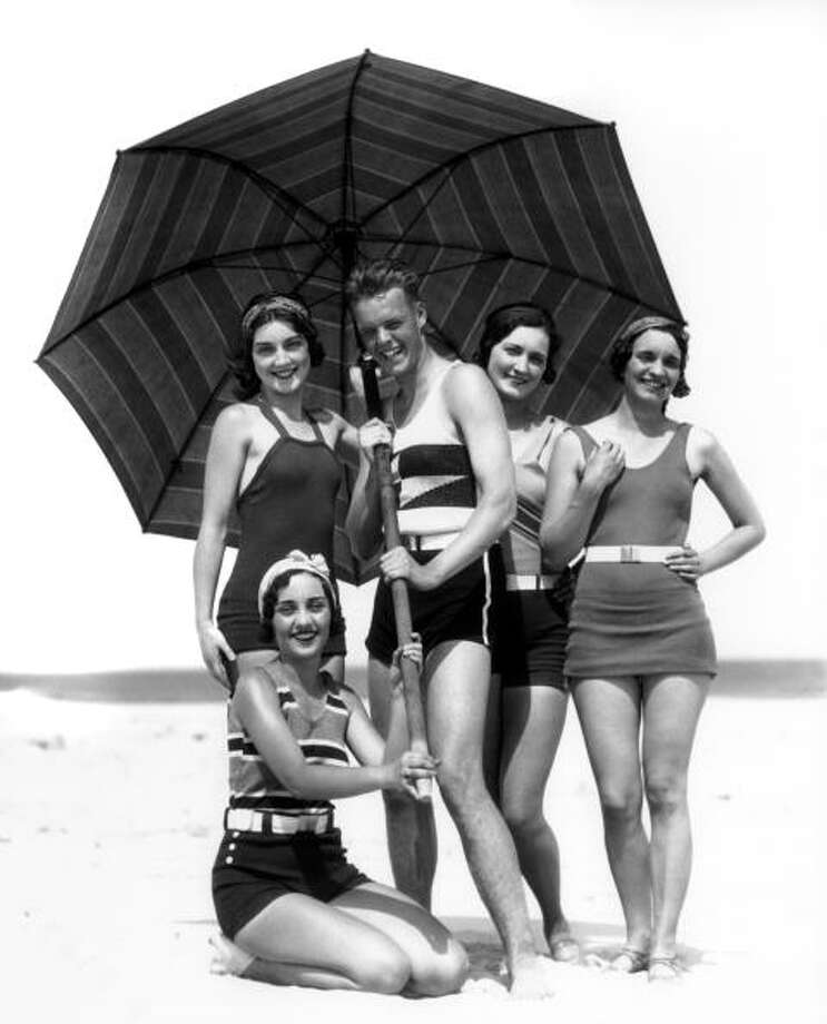 1930s:  Four women and one man under a beach umbrella in bathing suits, all are smiling.  Photo: H. Armstrong Roberts, Getty / Retrofile