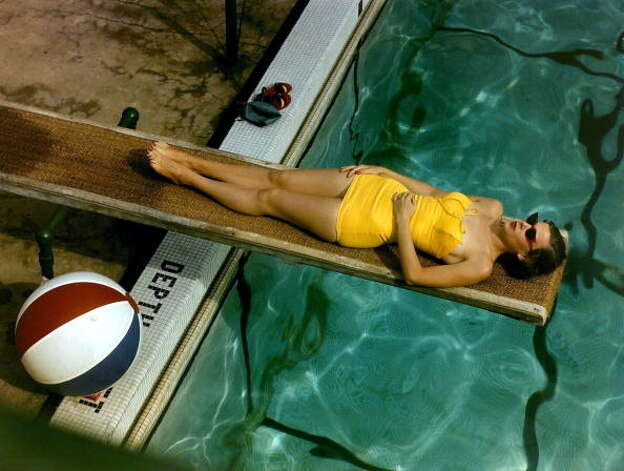 1950s: Woman wearing yellow swimsuit relaxing at the poolside Photo: Paul Popper/Popperfoto, Getty / Popperfoto