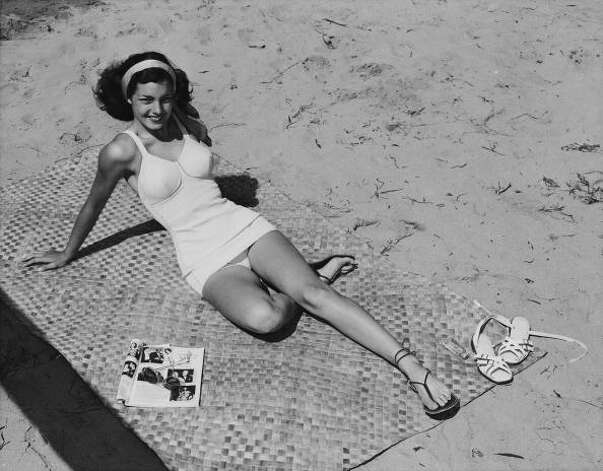 1955: A young woman in a one-piece swimsuit relaxes on a beach. Photo: Archive Photos, Getty / 2009 Getty Images