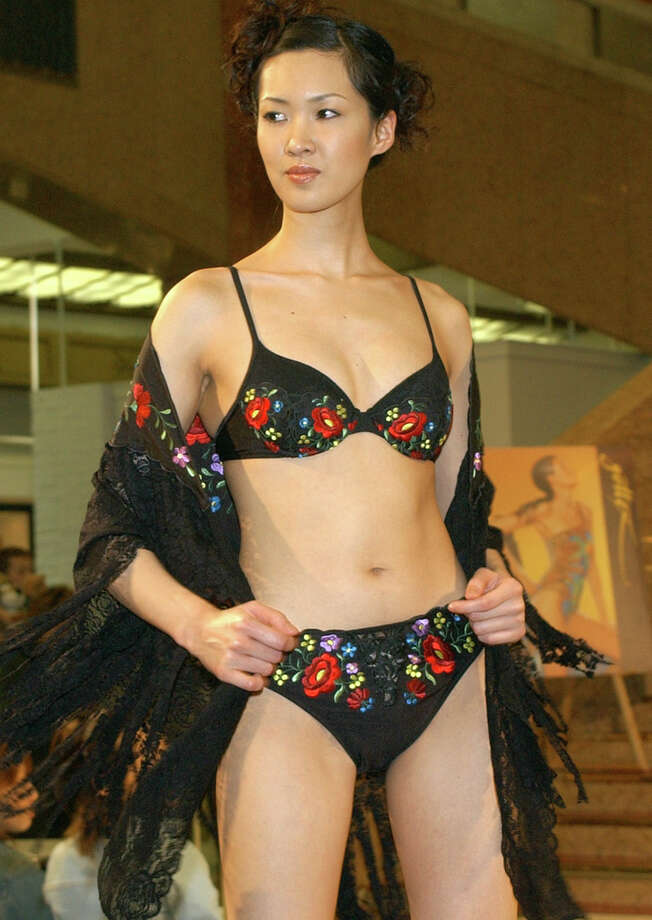 2003:A model displays a flower-patterned black bikinis with matching sarong.  Photo: KATSUMI KASAHARA, Getty / AP