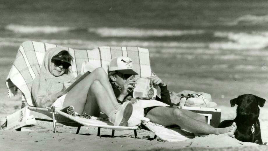 March 14, 1988: Mother Nature took an uncooperative approach Monday to students trying to enjoy spring break in the Galveston sunshine. Amy Muller and Scott Henries work on University of Houston term papers while braving chill winds on the beach in the company of a canine companion. Photo: Ben DeSoto, Houston Chronicle