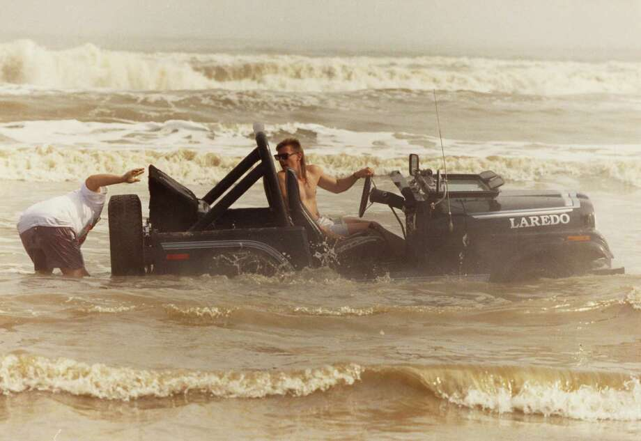 March 17, 1991: An unidentified would-be sailor tries to extract his Jeep from the surf on West Beach where crowds of spring breakers finally got a glimpse of sunshine. Photo: Gaylon Wampler, Houston Chronicle