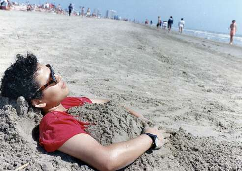 Spring breaker Ana Orellana of Houston found the Galveston sand to be just the right cover-up for today s bright skies. Near Stewart Beach. March 14, 1992 Photo: Manuel M. Chavez, Houston Chronicle