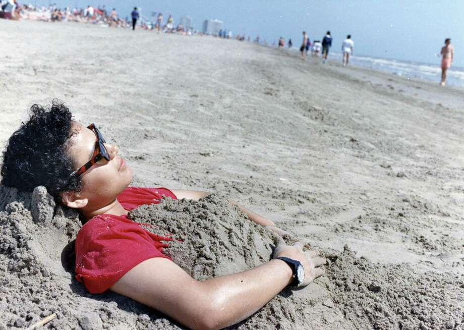 March 14, 1992:Spring breaker Ana Orellana of Houston found the Galveston sand to be just the right cover-up for the bright skies near Stewart Beach. Photo: Manuel M. Chavez, Houston Chronicle