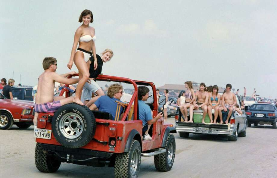March 13, 1988: Lee High School student Colleen McCormack rides on top of a Jeep driven by Bill Moore in Houston. Thousands of students spent Saturday at Galveston's East Beach. Photo: Houston Chronicle