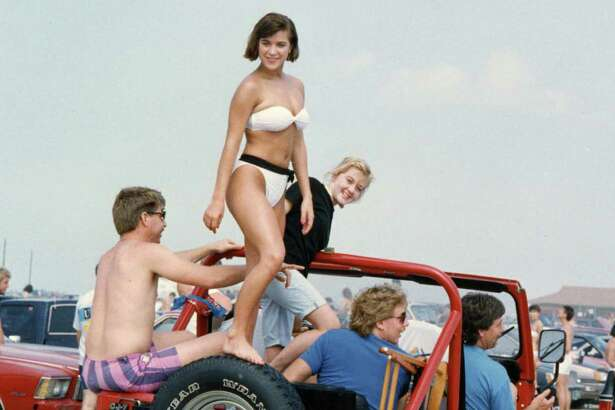 Riding on top of Jeep is Colleen McCormack of Lee High School in Houston. Thousands of students spent Saturday at Galveston s East Beach. Jeep s driver is Bill Moore. March 13, 1988.