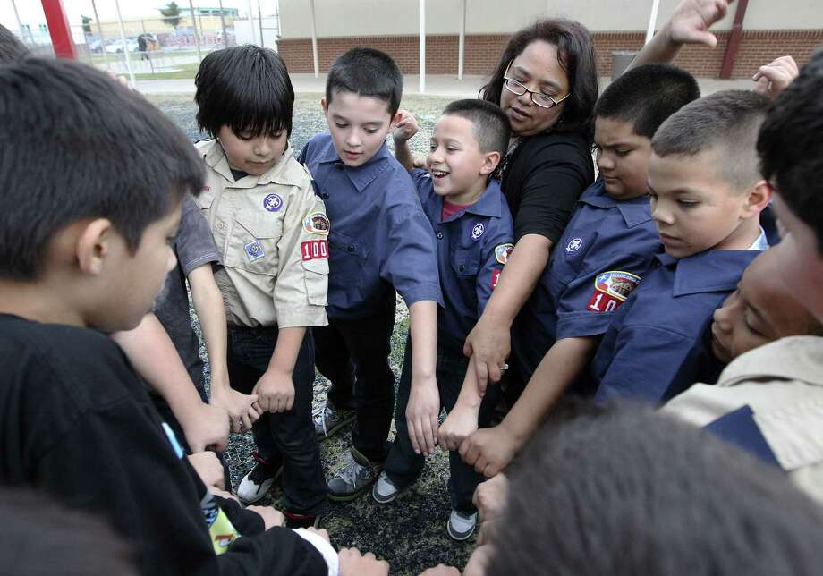 "Pack 1004 leader Yvonne Johnson joins her Scouts in the ""ring of life"" during a recent meeting at Columbia Heights Elementary. Photo: Photos By Kin Man Hui / San Antonio Express-News"