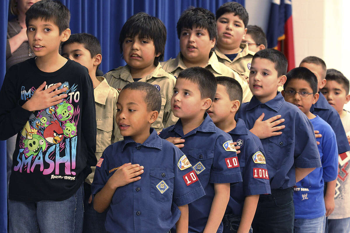 The Scouts recite the Pledge of Allegiance at the start of a PTA meeting.