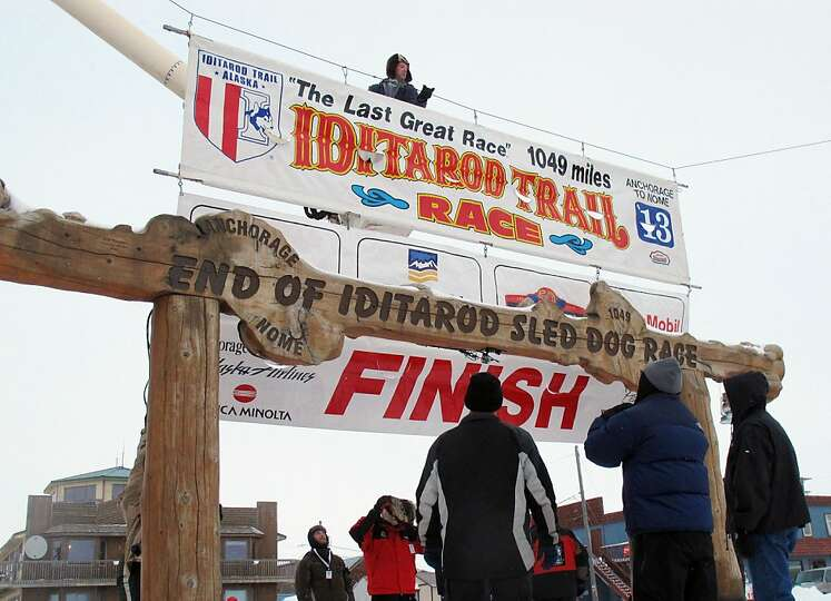 Volunteers hang a banner above the burled arch, which serves as the finish line for the 1,000-mile I