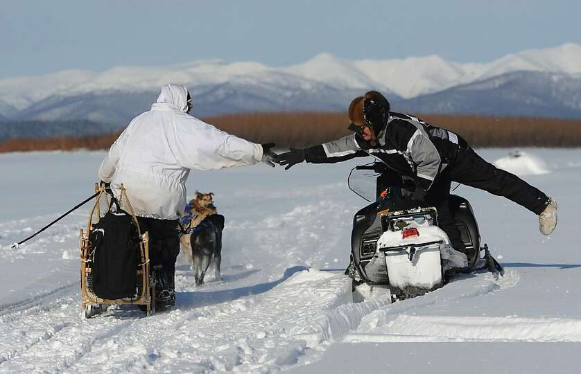 Four-time Iditarod champion Martin Buser reaches out to long-time friend and Nulato checker Larry Es
