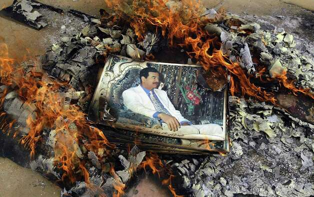 An image of Saddam Hussein is burned by U.S. Marines on April 7, 2003. Photo: File Photo, Getty Images / 2003 Getty Images