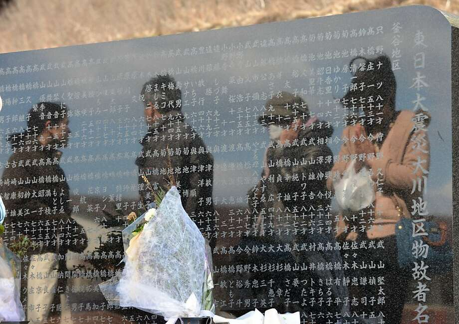 People are reflected in the stone as they visit a memorial alter to pray at the Okawa elementary school, where at least 70 students died in the 2011 tsunami, in Ishinomaki, Miyagi prefecture on March 11, 2013.  Japan on March 11 marked the second anniversary of a ferocious tsunami that claimed the lives of 15,881 people, with 2,668 others remaining unaccounted for, and sparked the worst nuclear accident in a generation.  Photo: Toshifumi Kitamura, AFP/Getty Images