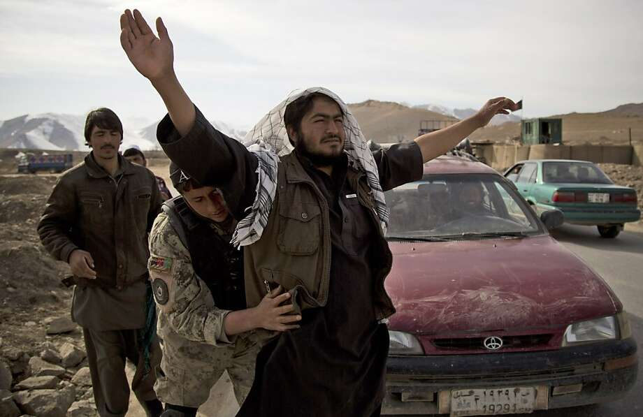 Afghan National Civil Order Police check passengers at a checkpoint on the outskirts of Maidan Shahr, Wardak province, Afghanistan, Sunday, March 10, 2013. Afghan President Hamid Karzai, infuriated by villager reports of forced detentions and mass arrests, gave U.S. Special Forces two weeks to vacate Wardak province, located barely 30 kilometers (24 miles) from the Afghan capital of Kabul. The deadline for their withdrawal expired midnight Sunday, March 10, 2013.  Photo: Anja Niedringhaus, Associated Press