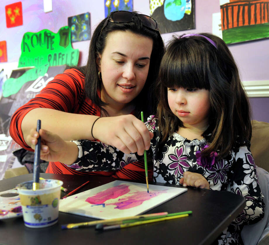 Adrienne Kraus, of Newtown, and daughter, Rachel, 4, paint butterfies together Monday afternoon. To honor Sandy Hook victim Dylan Hockley's seventh birthday on March 8, the SHACK (Sandy Hook Arts Center for Kids) held a Purple Butterflies event at the studio in Sandy Hook, Conn. Monday, March 11, 2013. Photo: Carol Kaliff / The News-Times