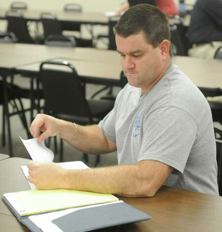 Kelly High School head football coach Clint Hartsfield looks over his schedule and the realignment paperwork. The high school sports realignment from the UIL was released at 9:00 am Thursday morning. Coaches from the area gathered at the Region 5 education service center in Beaumont for the release of the districts and to plan scheduling of games for next season.  Dave Ryan/The Enterprise Photo: Dave Ryan